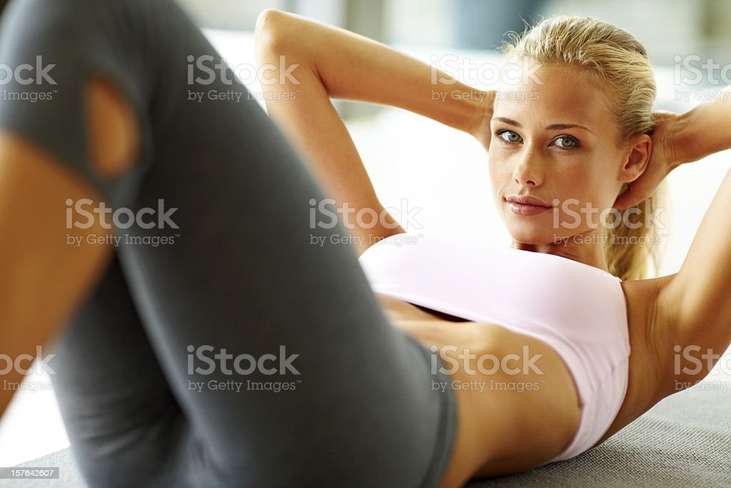 Pretty young lady doing abs exercise stock photo