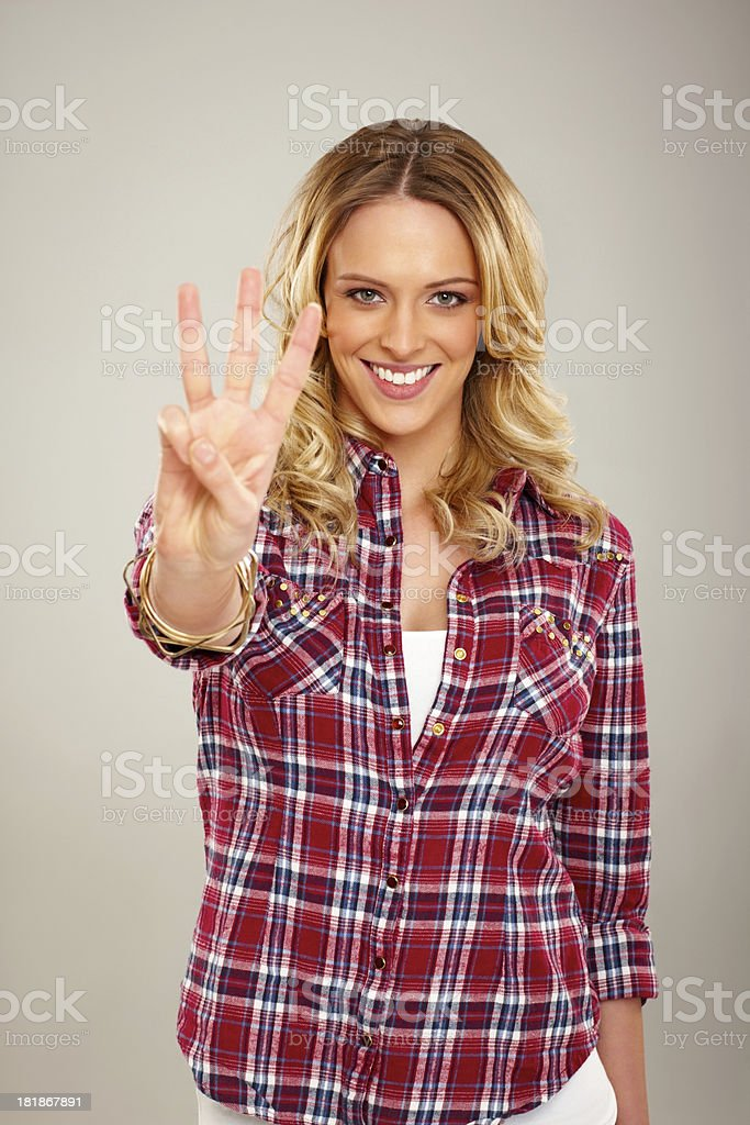 Pretty young lady showing three fingers stock photo