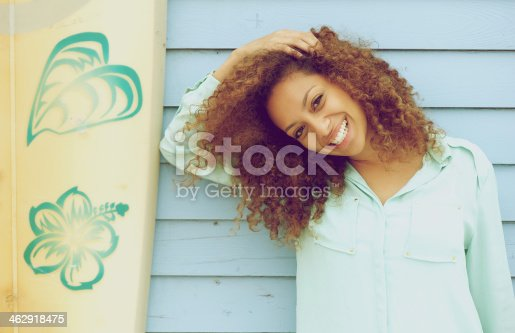 186534921 istock photo Pretty young lady smiling and leaning on surfboard 462918475