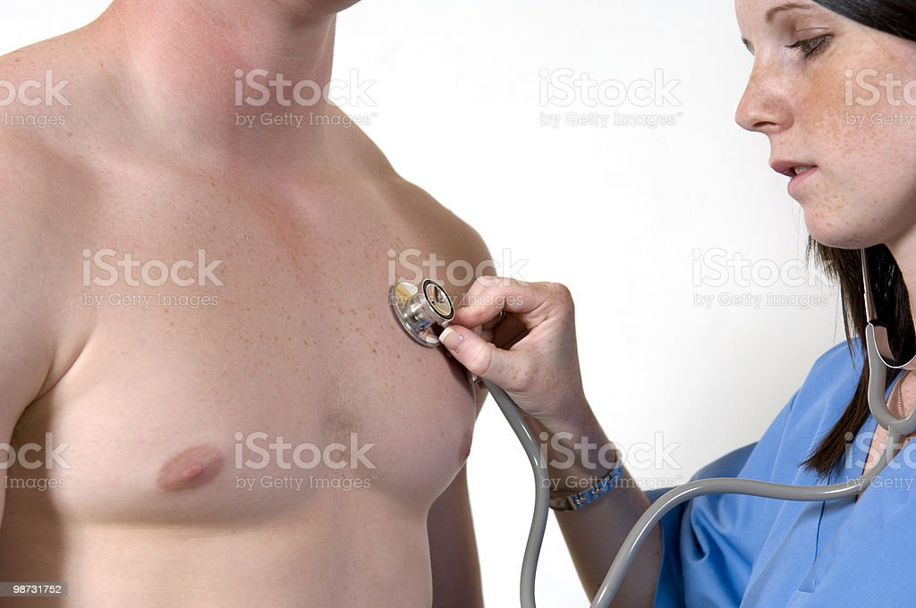 Pretty young nurse listens to a patient's heart beat royalty-free stock photo