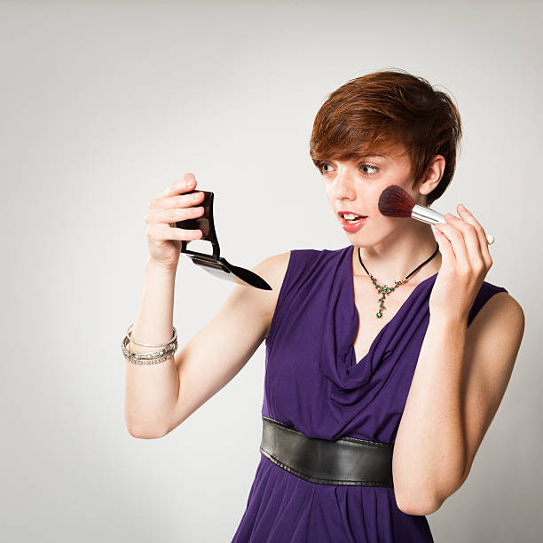 Pretty Young Red-Haired Woman Applying Makeup stock photo