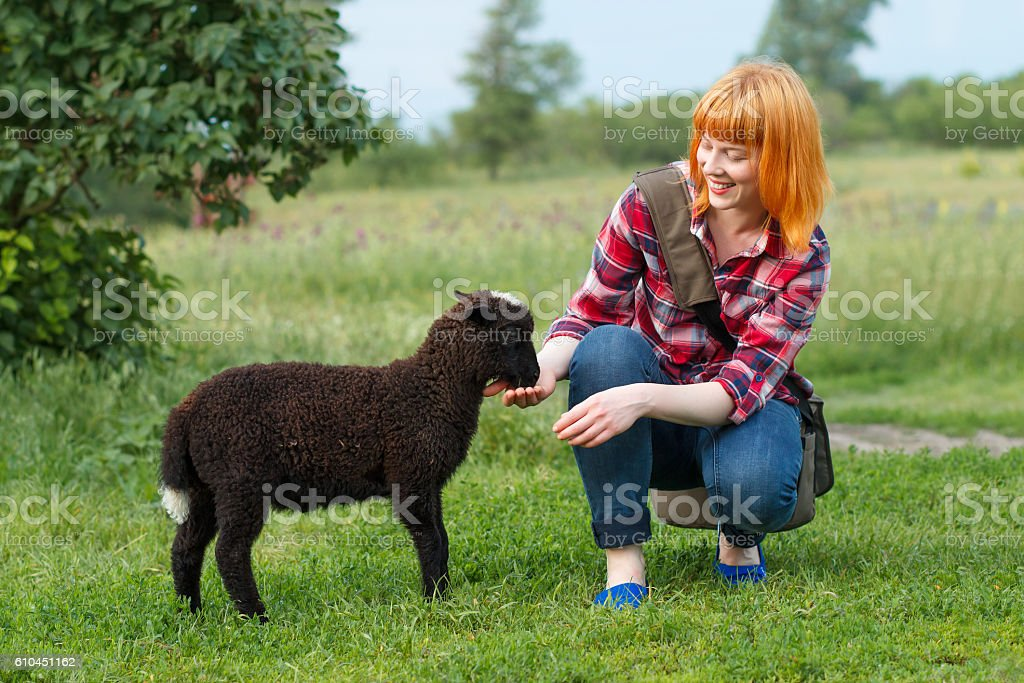 Pretty young red-haired woman feeding a black lamb – Foto
