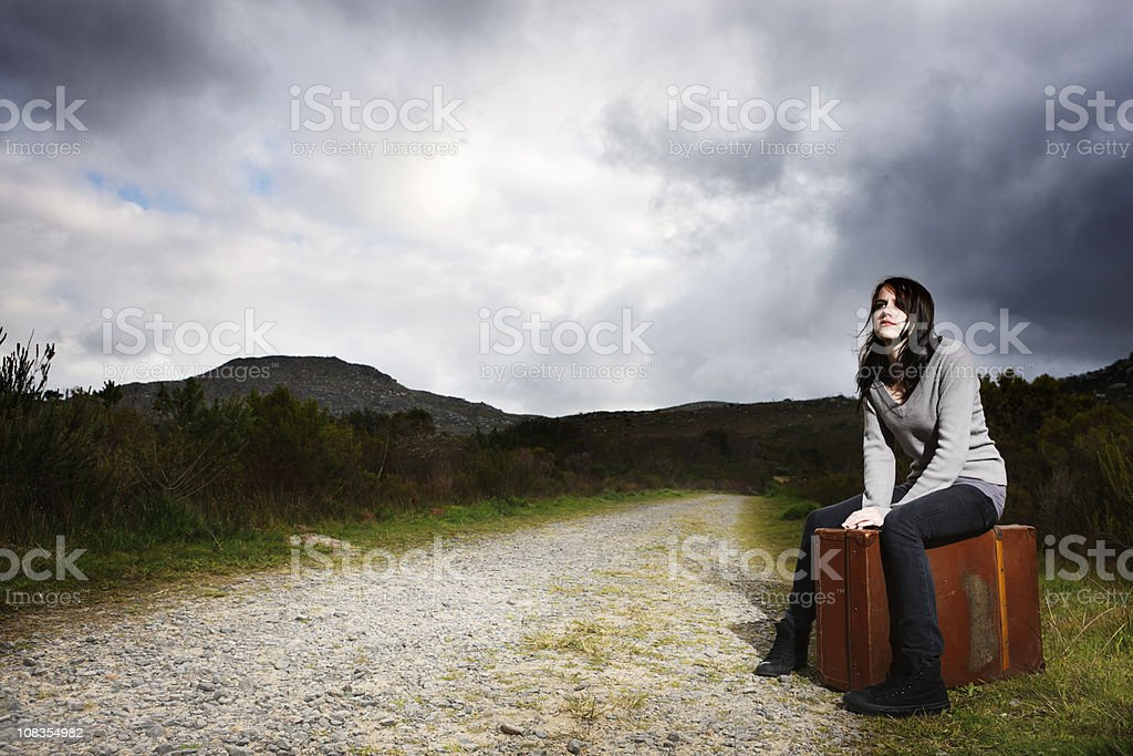 Pretty young runaway hitchhiker sits on her case at roadside royalty-free stock photo