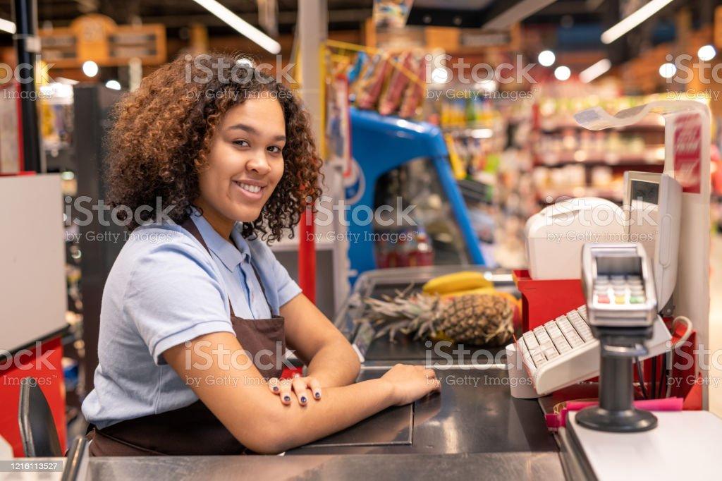 Hübsche junge Verkäuferin in Schürze sitzen an der Kasse im Supermarkt - Lizenzfrei Afrikanischer Abstammung Stock-Foto