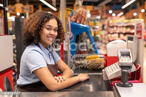 Pretty young sales clerk in apron sitting by cash register in supermarket and looking at you with smile while serving clients