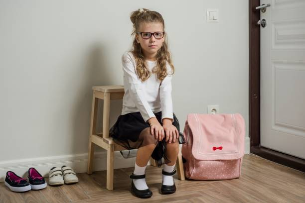 a pretty young schoolgirl with blond hair going to school, sitting next to the door - going inside eye imagens e fotografias de stock