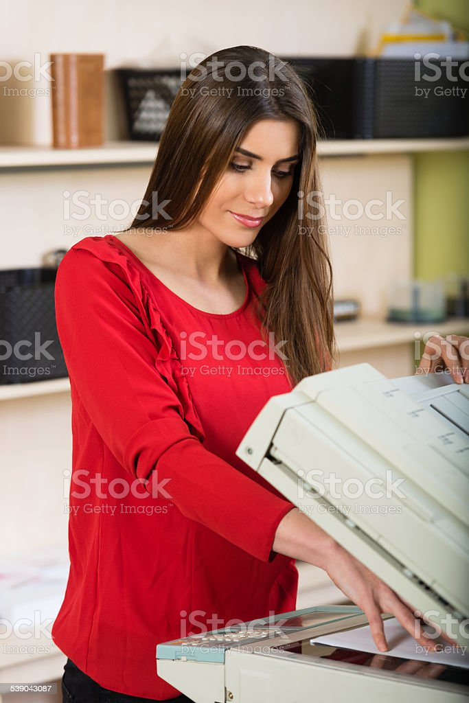 Pretty young secretary using a copy machine stock photo