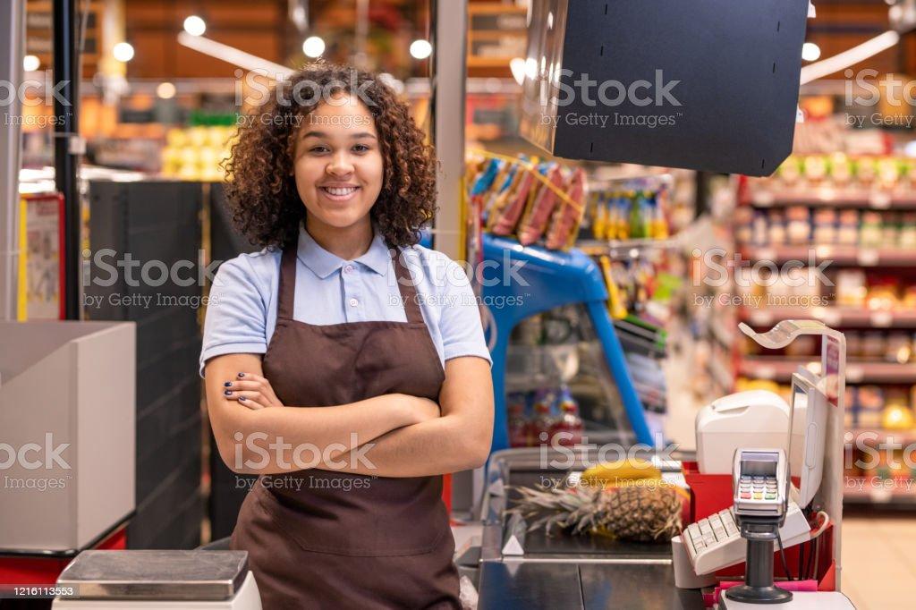 Ziemlich junge lächelnde afroamerikanische Verkäuferin, die Sie anschaut - Lizenzfrei Afrikanischer Abstammung Stock-Foto