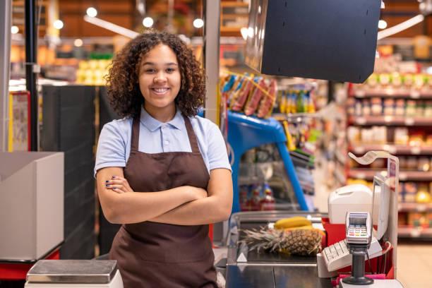Bastante joven sonriendo afroamericano mujer vendedora mirando a usted - foto de stock