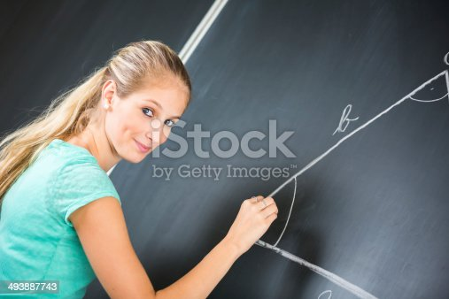 929797156 istock photo Pretty young teacher writing on the blackboard 493887743