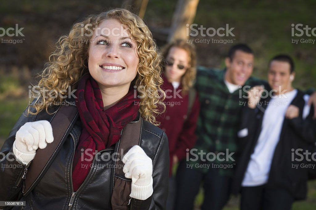 Pretty Young Teen Girl with Boys Behind Admiring Her royalty-free stock photo