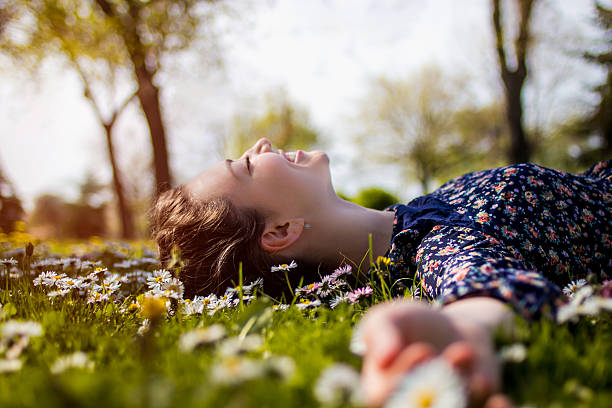 pretty young teenage girl relaxing on a grass - reclining stock photos and pictures