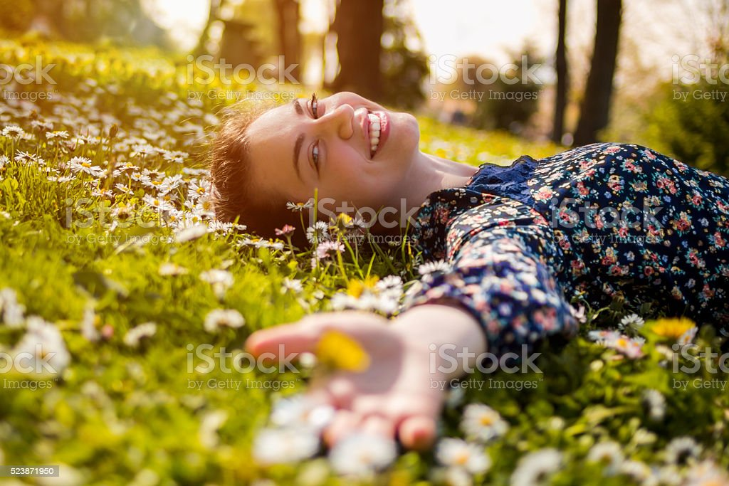 Pretty young teenage girl relaxing on a grass stock photo