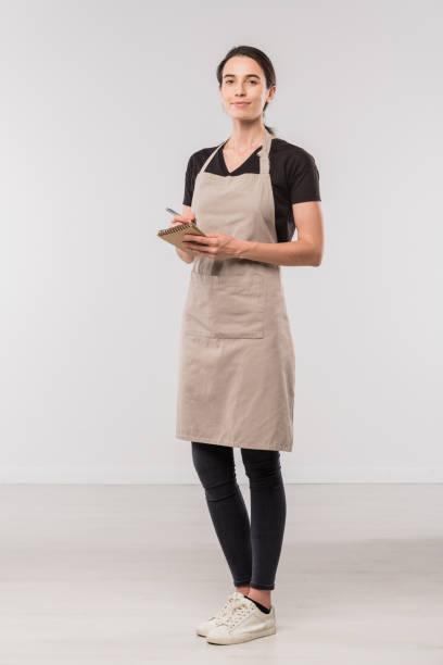 Hübsche junge Kellnerin des Cafés notizen über die Reihenfolge der Kunden in Isolation – Foto