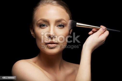 istock Pretty young woman applying make up with a brush 480288897