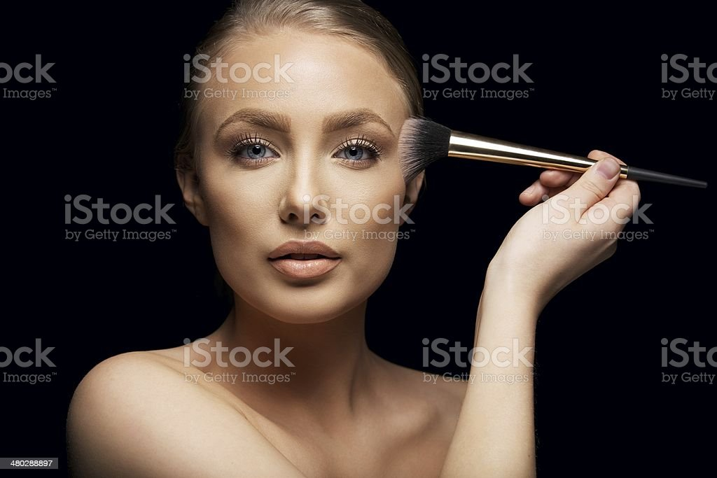 Pretty young woman applying make up with a brush stock photo