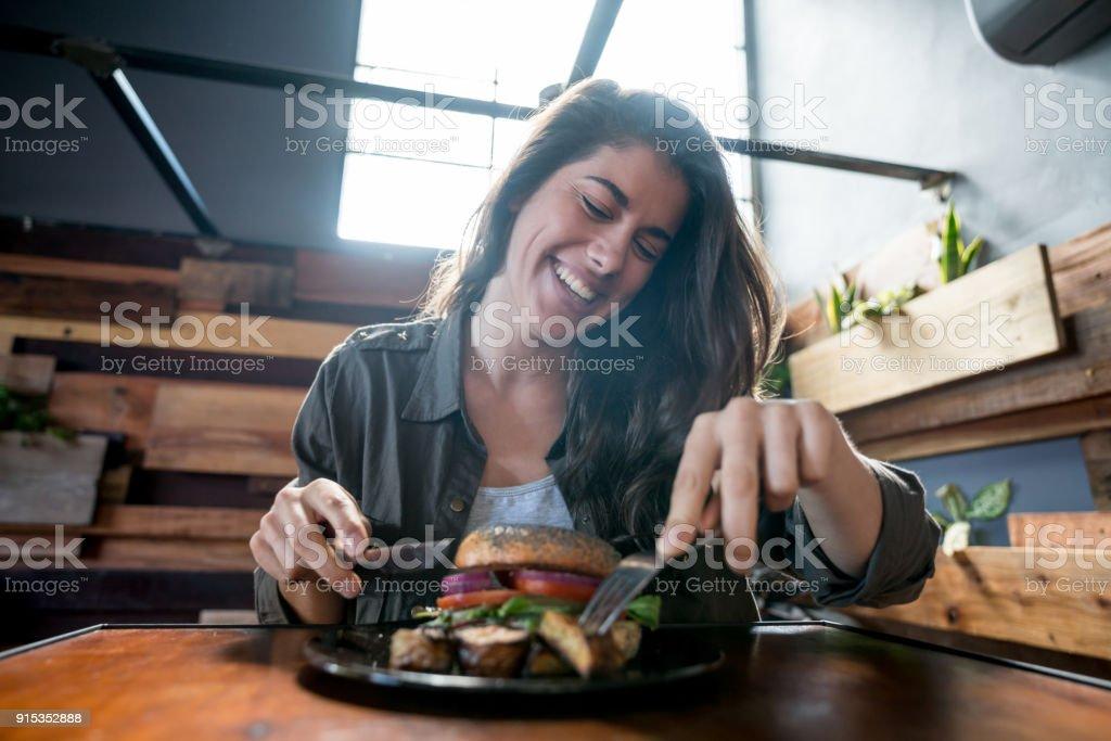 Muito jovem mulher em um restaurante rindo e desfrutando de um hambúrguer delicioso - foto de acervo