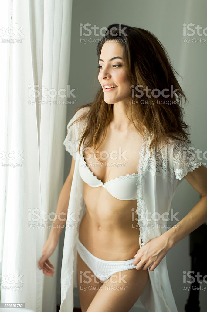Pretty young woman by the window royalty-free stock photo