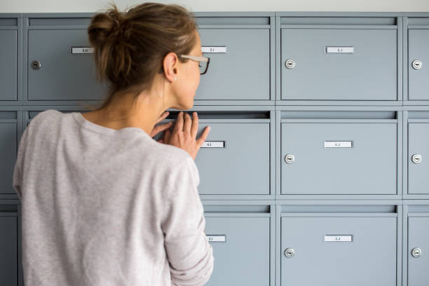 Pretty, young woman checking her mailbox for new letters Pretty, young woman checking her mailbox for new letters mailbox stock pictures, royalty-free photos & images