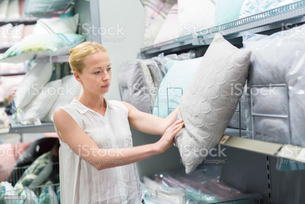 Hübsche, junge Frau, die dekorative Kissen für ihr Sofa in einem modernen Heimtextilien Shop auswählen. – Foto