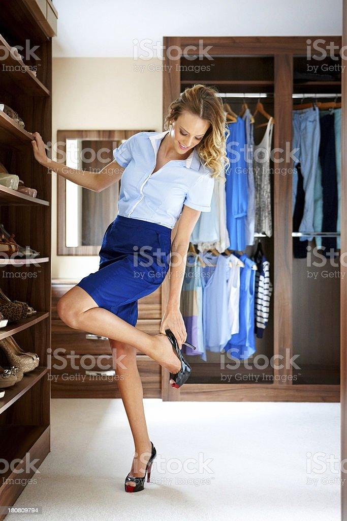 Pretty young woman choosing shoes to wear stock photo