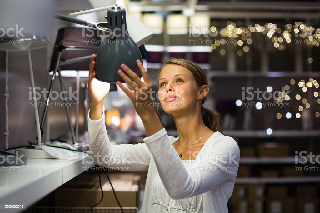 Pretty, young woman choosing the right light for her apartment stock photo