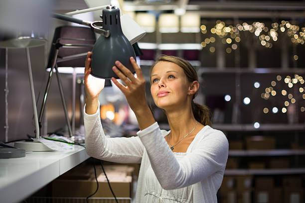 pretty, young woman choosing the right light for her apartment - furniture shopping stock photos and pictures