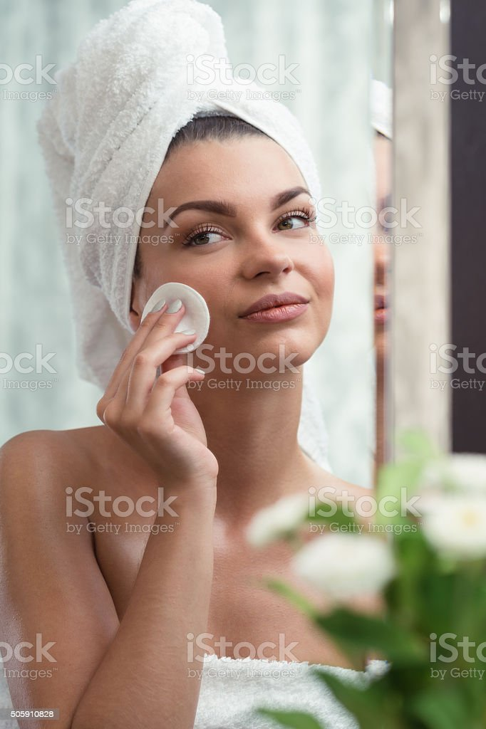 Pretty young woman creaming face stock photo