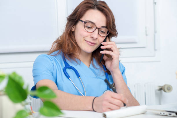 pretty young woman doctor talking on the phone - nurse on phone stock photos and pictures