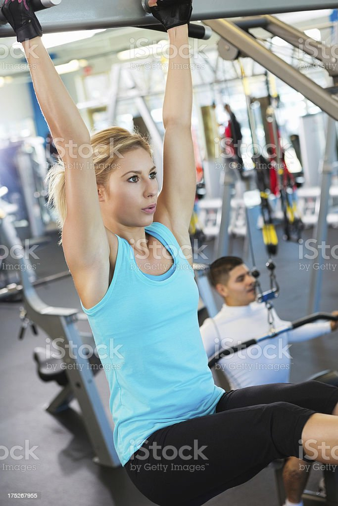 Pretty young woman doing pull-ups working out in gym royalty-free stock photo