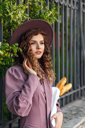 Pretty young woman dressed in French style with baguette in hand. French female style Paris. Close-up in stylish clothes holding fresh bread baguettes and smiling. Copy space for site or banner