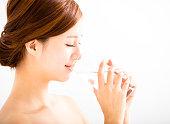 美しい若い女性の飲料水のガラス