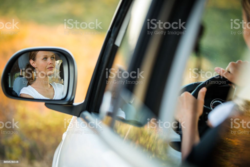 Pretty, young woman  driving her car stock photo