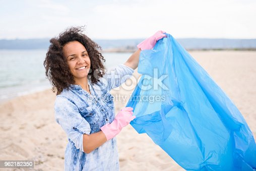 962184460 istock photo Pretty young woman during local clean up at the beach 962182350