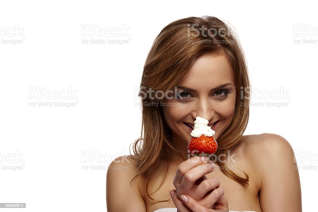 Pretty young woman eating a strawberry topped with cream stock photo
