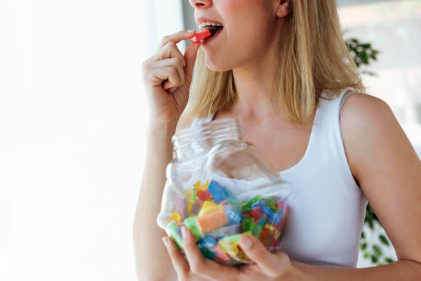 Pretty young woman eating colorful jelly candies at home. Addiction concept. stock photo