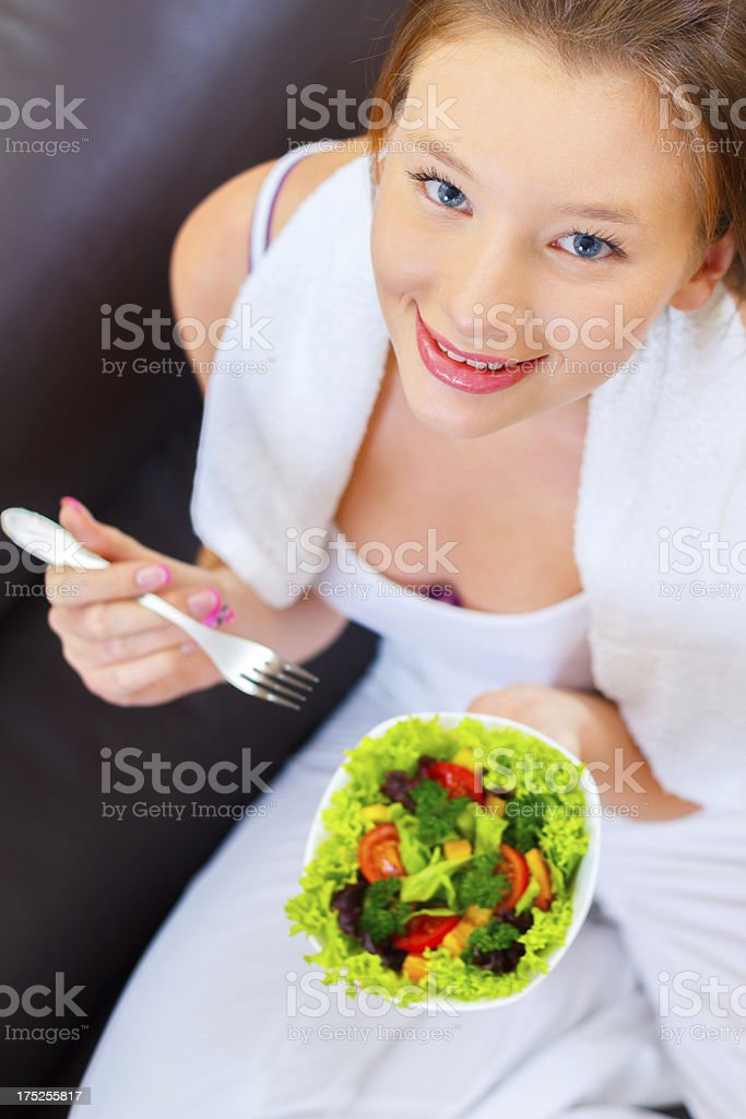Pretty young woman eating green vegetable salad royalty-free stock photo