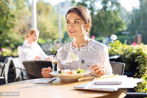 istock Pretty young woman eating out on restaurant terrace 854562688