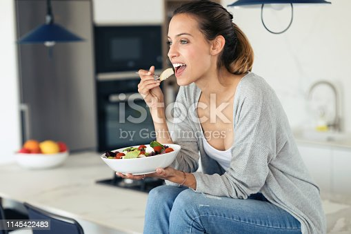 Shot of pretty young woman eating salad while sitting in the kitchen at home.