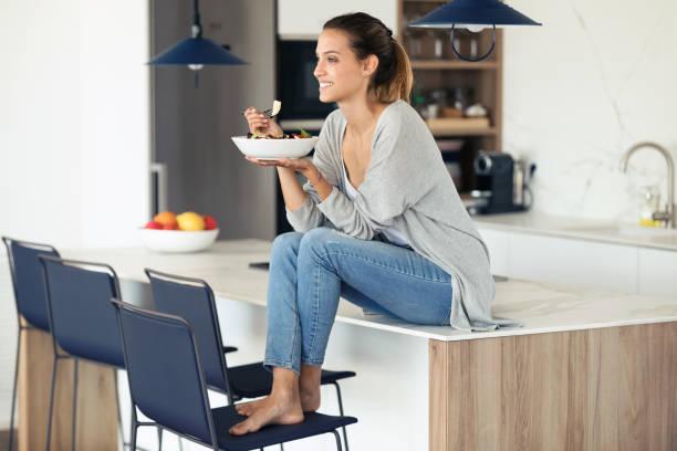 Hübsche junge Frau isst Salat, während sie zu Hause in der Küche sitzt. – Foto