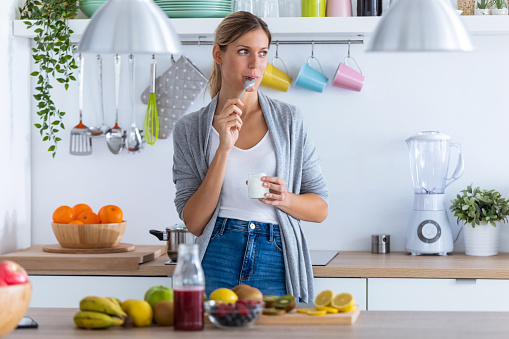 istock Pretty young woman eating yogurt while standing in the kitchen at home. 1190896660