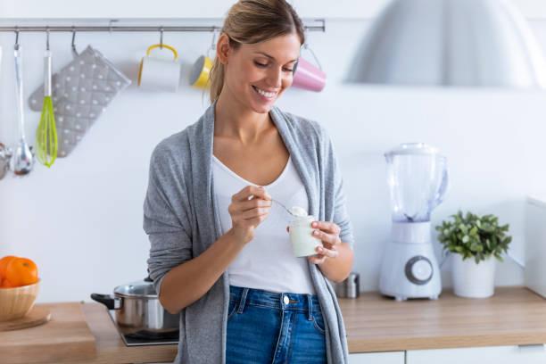 Hübsche junge Frau, die Joghurt isst, während sie zu Hause in der Küche steht. – Foto