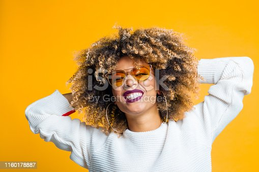 521083232istockphoto Pretty young woman enjoying on yellow background 1160178887