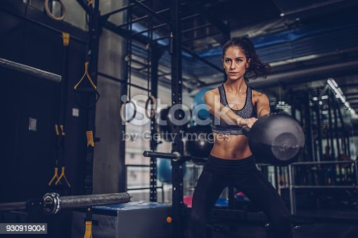 Young beautiful woman exercising with kettlebell in the gym