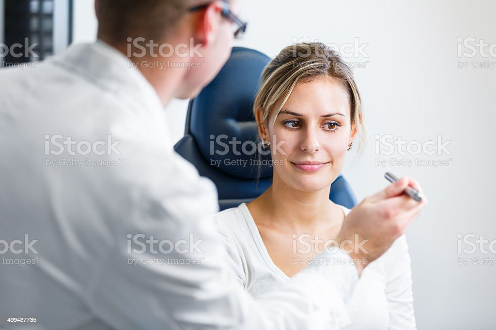 Pretty young woman having her eyes examined by optometrics stock photo