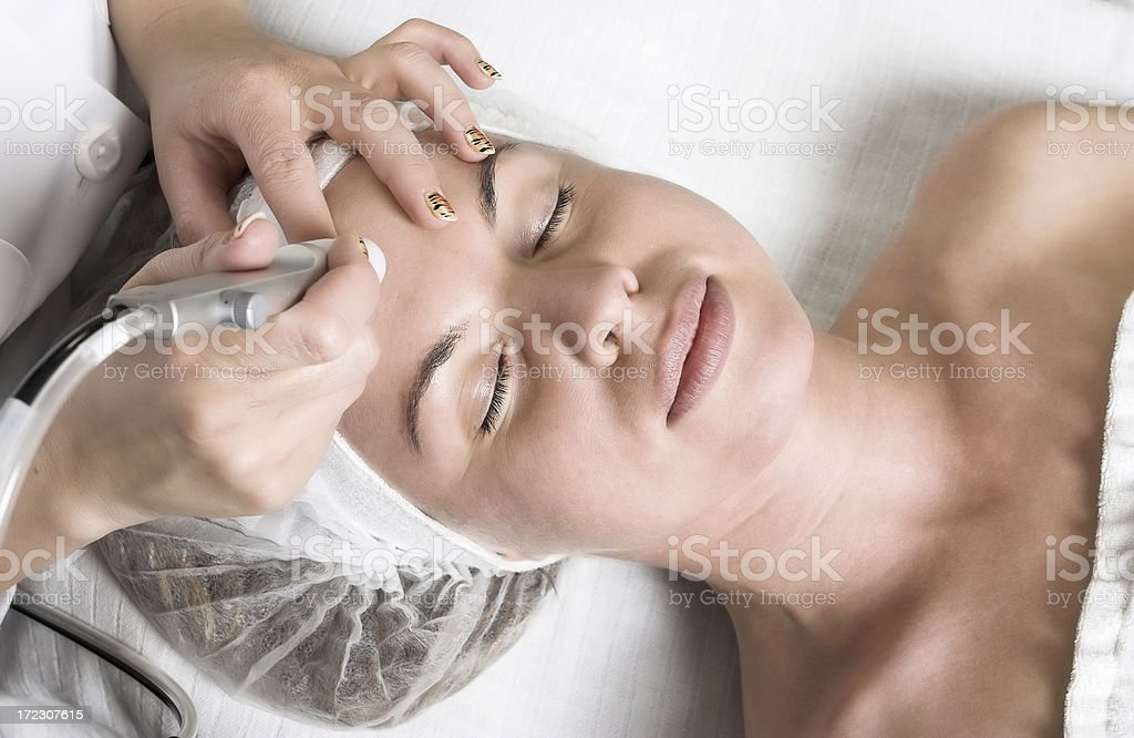 Pretty young woman having relaxing vitalizing face treatment stock photo