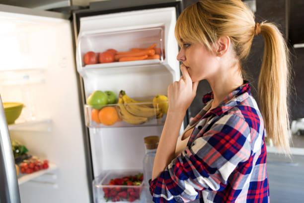 hübsche junge frau zögerlich, sich vor dem kühlschrank in der küche essen. - fett nährstoff stock-fotos und bilder