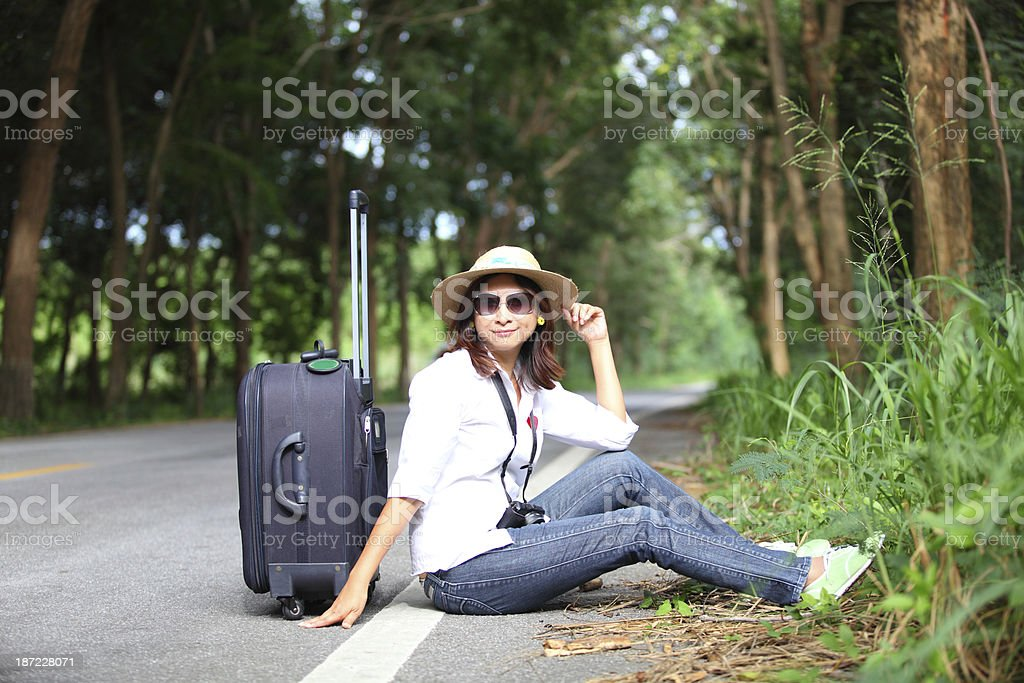 Pretty young woman hitchhiking along a road royalty-free stock photo