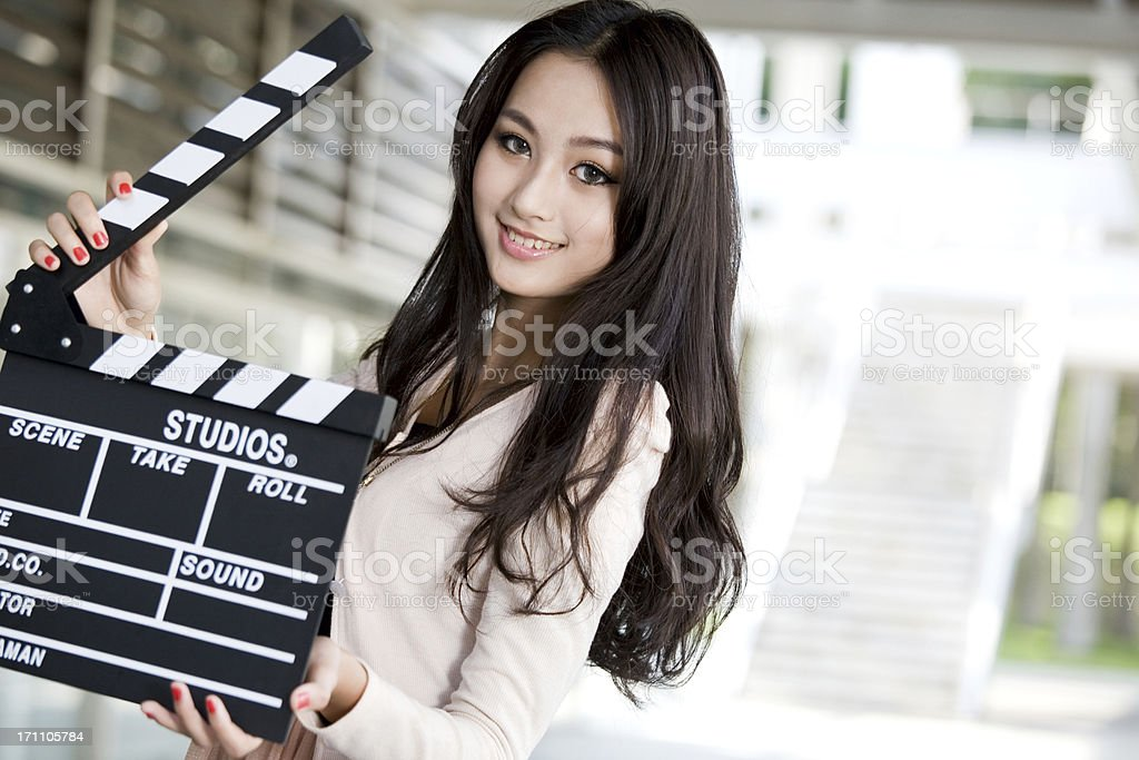 Pretty young woman holding a clapper royalty-free stock photo