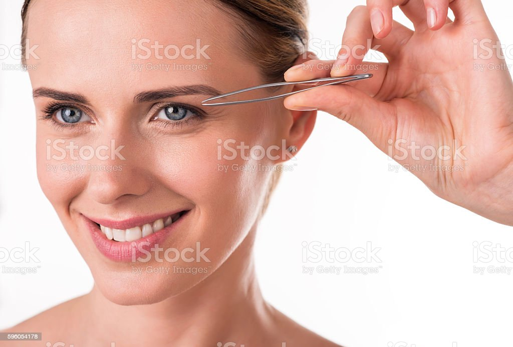Pretty young woman holding tweezers royalty-free stock photo